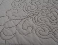 Close up view of the fleur-de-lis pattern on the Cavendish Cotton Quilt Set.