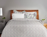 The reverse of the Brittany Floral Coverlet set features the same pattern as the front, muted purple florals on a bed of green foliage with a white background in a smaller and tighter print.
