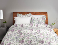 The Brittany Floral Coverlet Set features muted purple florals on a bed of green foliage with a white background.