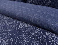 Close up of Sumatra bedding collection; a beautiful silver batik design on a bed of sapphire blue.