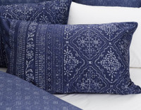 The silver diamond medallion pattern is delicately patterned on a sapphire blue background.