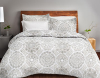 Adan Coverlet Set features a medallion print in mixed shades of grey and brown on a white background.