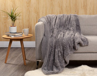 Faux Rabbit Plush Throw pictured in Graphite Grey on couch