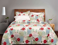 Noel Coverlet Set, featuring red and white script and bold red poinsettias on a patchwork background in white, pale blue, and light green.