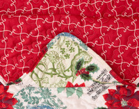 Noel Coverlet Set, featuring red and white script and bold red poinsettias on a patchwork background in white, pale blue, and light green. This festive design reverses to a bold red with cream filigree design
