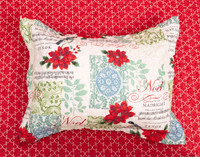 Noel Pillow Sham featuring bold red poinsettias on a patchwork background in white, pale blue, and light green.
