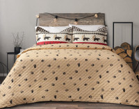 The Trailhead Coverlet Set reverses to a beige background with black pawprints