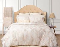 Mirasol Bedding Collection in beige with gold pattern in a white bedroom