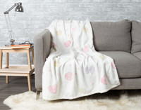 Shine Bright Glow in the Dark Throw pictured draped over a couch.