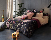 Monika Bedding Collection featuring romantic pink and purple florals on a dark blue background in a modern room.