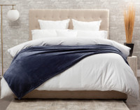 The Cashmere Touch Fleece Blanket pictured in Indigo, a deep, dark blue.