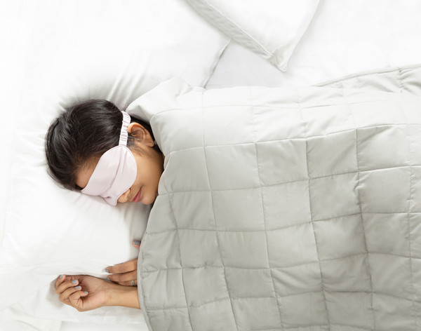 Woman sleeping in a bed with a Balance Weighted Blanket