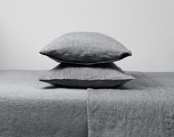 Vintage Washed European Linen Pillowcases stacked vertically on a bed.