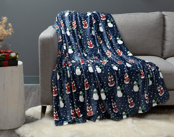 Penguins Holiday Throw draped over a modern couch.
