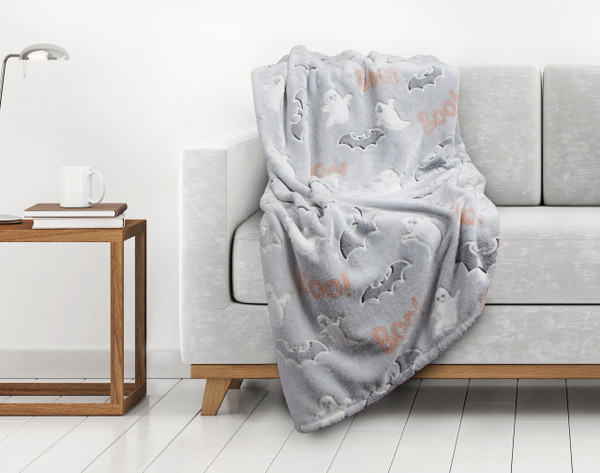Boo Glow In The Dark Fleece Throw draped over a couch.