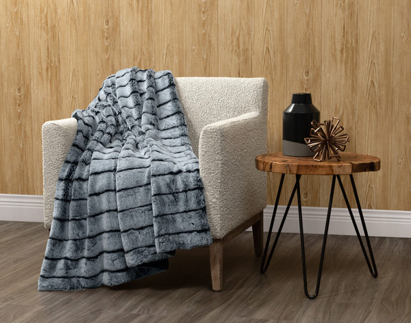 Tip-Dyed Faux Fur Throw in Sea Storm draped over a living room chair.