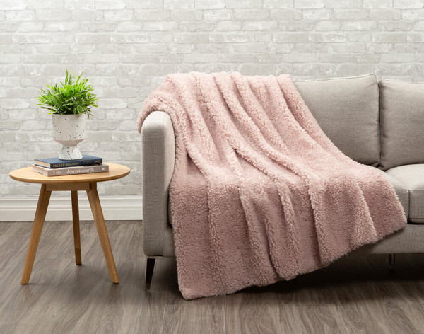Sherpa side of Lambswool Faux Fur Throw in Blush draped over a living room chair.