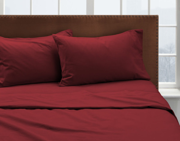 Our Rhubarb Flannel Sheet Set dressed over a bed and pair of pillows.