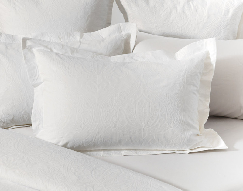 Astoria White Pillow Sham with two inch flange on bed