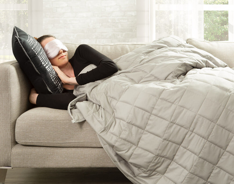 Woman sleeping on the couch with a Balance Weighted Blanket