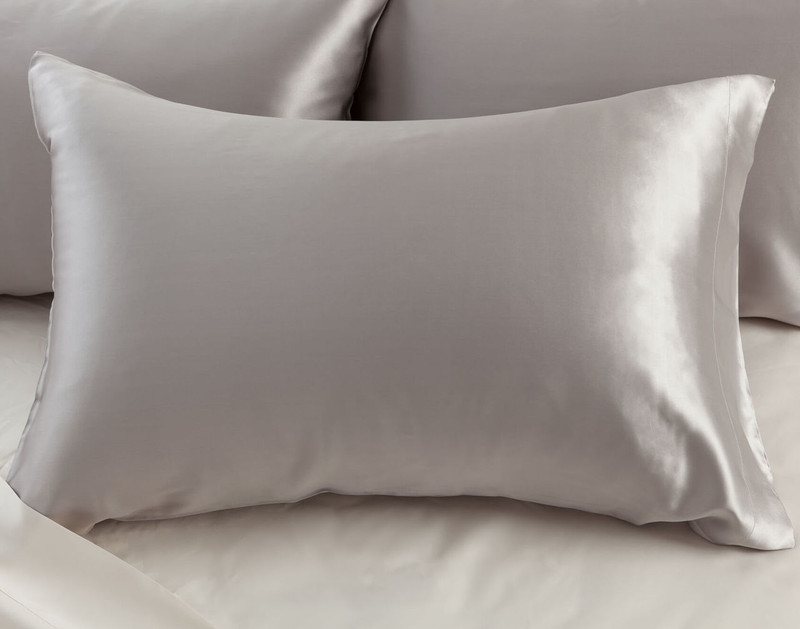 100% Mulberry Silk Pillowcase in Silver on bed.