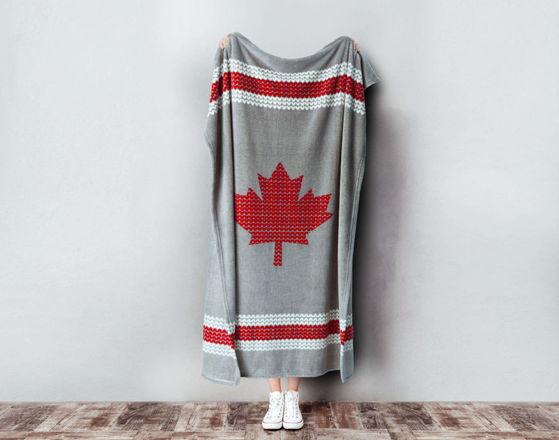 Chalet Sock Canada Fleece Throw being held up.