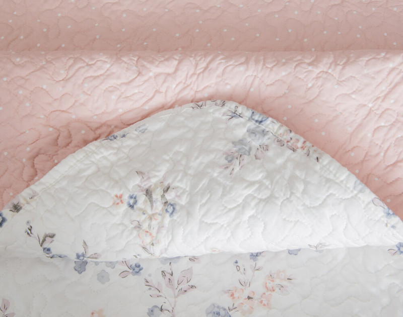 Close up of the light pink reverse side prin and edge detailing on the Annalise Cotton Quilt Set.