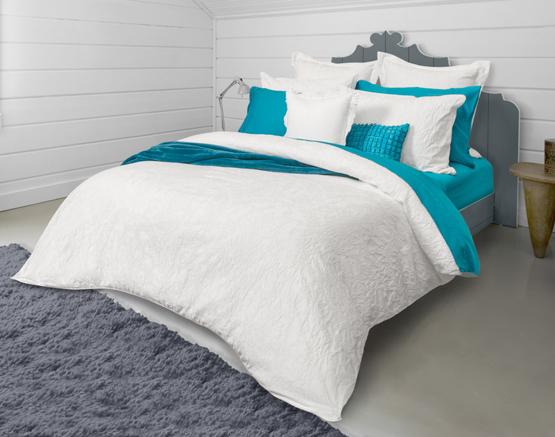 Side angle view of the Palma Bedding Collection styled with aquamarine sheets.