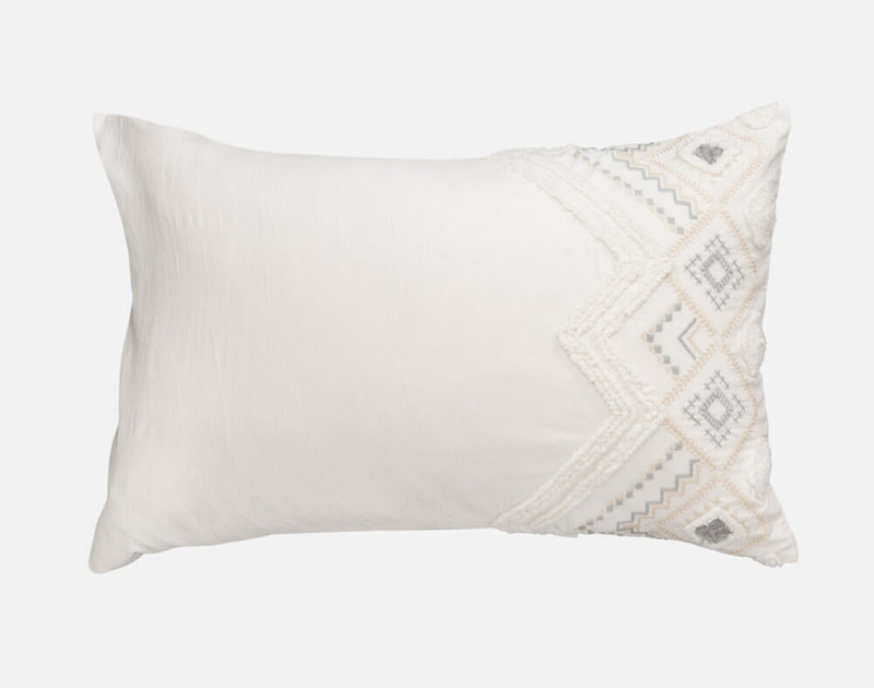 The Charity Duvet Cover pillow sham features geometric embroidery on eggshell white.