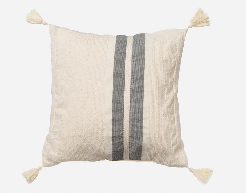Noa Square Cushion is an off-white accent piece that features two vertical stripes in charcoal grey, slightly off center, and has tassels in each corner.