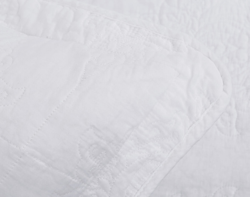 Close up of Marissa Cotton Quilt Sham's piped edges. Marissa is a white monochromatic collection with stitched damask pattern.