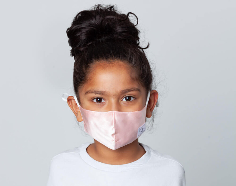 Front view of child wearing Blush Pink face mask.