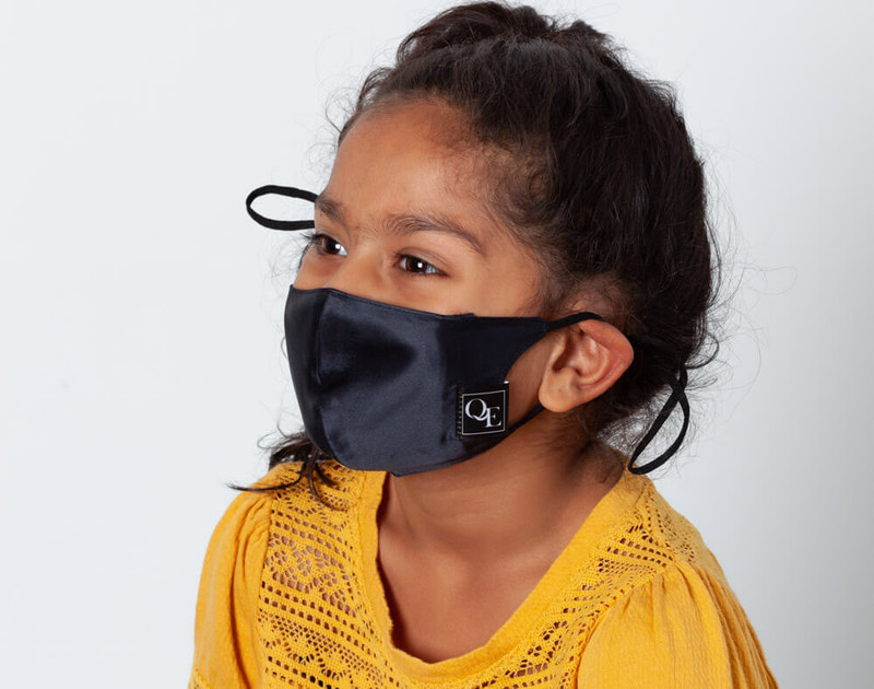 Picture shows a child wearing our Black silk face mask, side view.