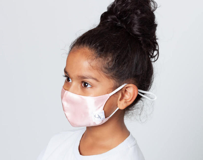 Picture shows a child wearing our Blush Pink silk face mask, side view.