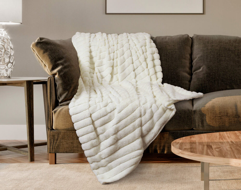The Ribbed Faux Fur Throw in White, looks luxurious draped across the couch.