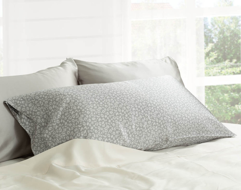 100% Mulberry Silk Pillowcases in Silver Leopard on bed.