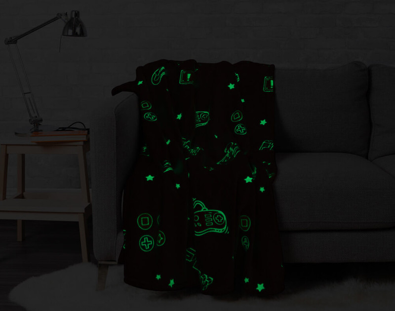 Game Over Glow in the Dark Throw pictured in the dark with glow in the dark portions lit up.