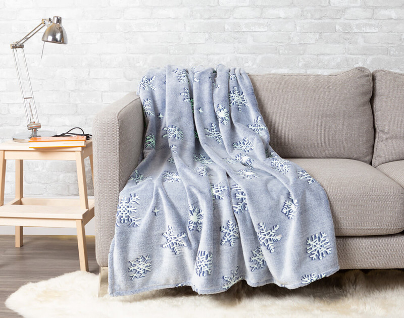 Snowfall Glow in the Dark Throw pictured draped over a couch.