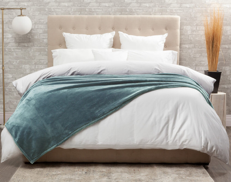 The Cashmere Touch Fleece Blanket pictured in Tidewater, a pastel blue-green.