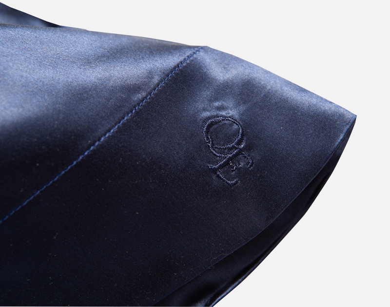Close up of stitched QE Home logo.
