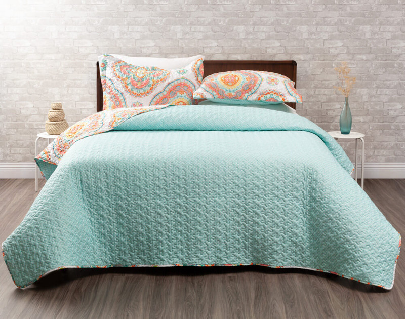 Marigold Coverlet Set reverses to a solid turquoise with small white flowers.