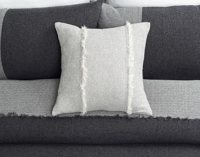 Thoren Square Cushion Cover laying over top Thoren Duvet Cover and Thoren Pillow Shams.