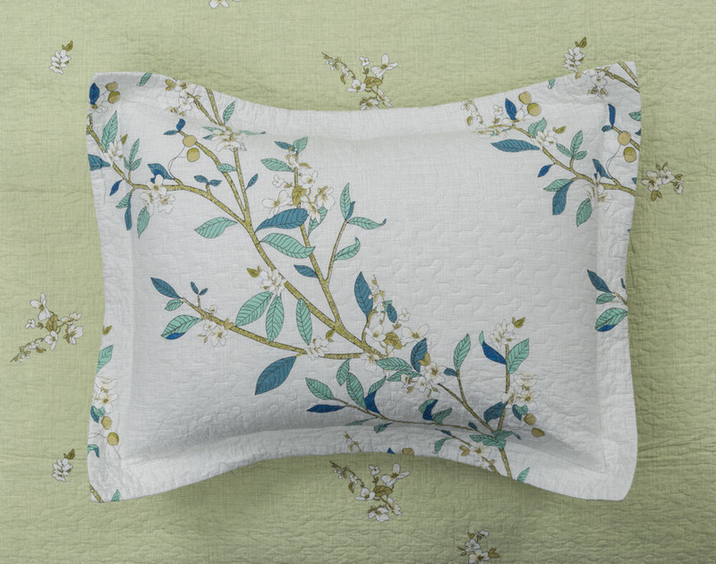 Josette Pillow Sham displayed on the reverse side of the quilt set, a light meadow green