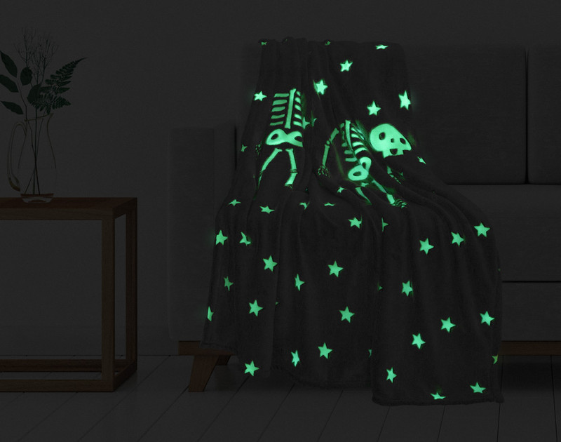 Skeleton Glow In The Dark Fleece Throw pictured in the dark with glowing bones and stars.