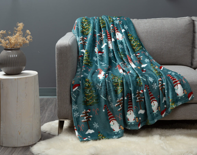 Believe Holiday Throw draped over a modern couch.