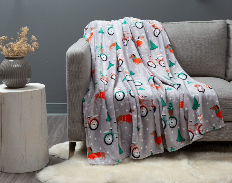 Dachshund Holiday Throw draped over a modern couch.