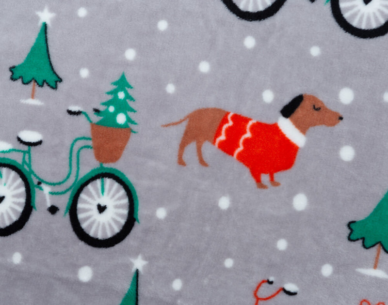 Close-up of Dachshund Holiday Throw pattern with adorable dogs and bicycles in the snow.