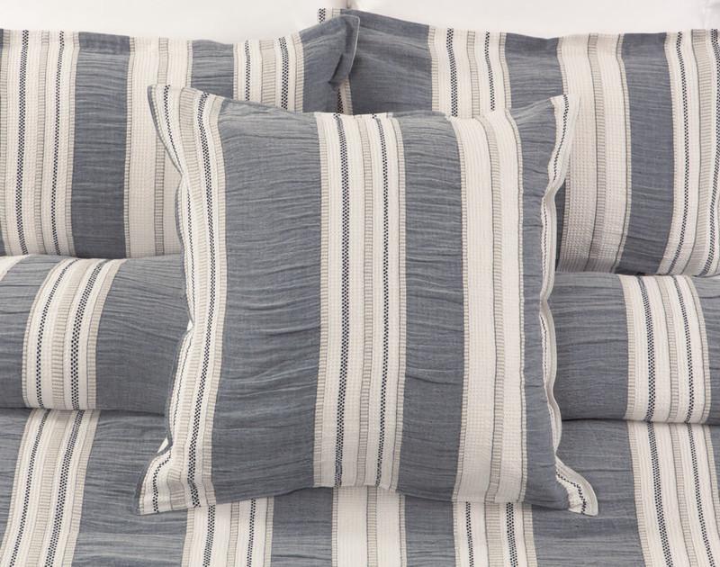 Truro Euro Sham in shades of cream and indigo grey on bed.