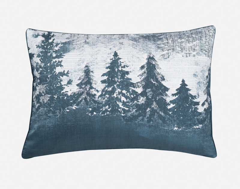 Close-up of our Alps Pillow Sham, featuring a dark and snowy forest design.