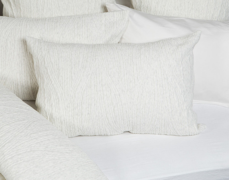 Everley Pillow Sham laying on half-open bedding.
